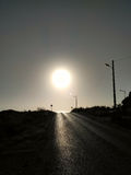 Black road and white sun, artistic photo Royalty Free Stock Images