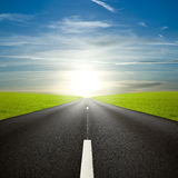 Black roadway against an amazing sunrise. Roadway and meadows against sunrise sunbeams royalty free stock images