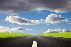 Black roadway against a nice cloudy sky Royalty Free Stock Photo