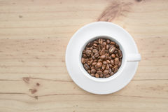 Black roasted arabica coffee beans. And cup full of coffee Royalty Free Stock Photo