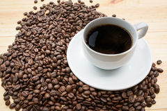Black roasted arabica coffee beans. And cup full of coffee Royalty Free Stock Image
