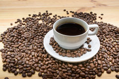Black roasted arabica coffee beans. And cup full of coffee Royalty Free Stock Photography