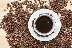 Black roasted arabica coffee beans. And cup full of coffee Royalty Free Stock Photos