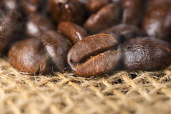 Black roasted arabica coffee beans. Image of a cup of black roasted arabica coffee beans with some smoke effect stock photo