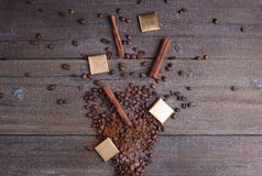 Black roasted coffee beans and grind with spices cinnamon, anise, cardamom, clove and brown sugar. With black vintage coffee grind Royalty Free Stock Images