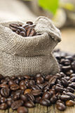 Black roasted coffee beans in a small burlap sack Stock Images