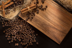 Black roasted coffee grains and cinnamon. On a wood background. Top view and frame for inscriptions. Stock Photography