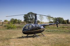 Black Robinson R44 helicopter parked on grass. DOBANOVCI, SERBIA - AUGUST 26, 2017: Black Robinson R44 helicopter parked on grass during World Helicopter Day Royalty Free Stock Images