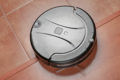 Black robotic vacuum cleaner runs on the laminate and on the tile floor Closeup. The robot is controlled by voice commands for dir. Ect cleaning. Modern stock photography