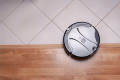 Black robotic vacuum cleaner runs on the laminate and on the tile floor. The robot is controlled by voice commands for direct clea. Ning. Modern technology of stock photo