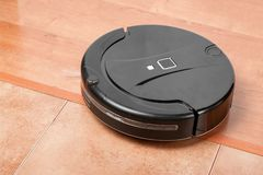 Black robotic vacuum cleaner runs on laminate and on tile floor. Robot controlled by voice commands for direct cleaning. Modern sm. Art appliance for cleaning stock photos