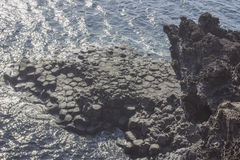 Black rock cliff shape and form volcano island with ocean Royalty Free Stock Images