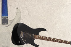 Black rock guitar and back of guitar body on light skin background, with plenty of copy space. Royalty Free Stock Photo