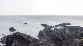 Black rock made from lava volcano island with ocean Stock Images