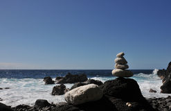 Black Rock with a Pebbles Pile with sea and blue sky Royalty Free Stock Image