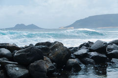 Black rock stone coast in front of rough windy sea Royalty Free Stock Image