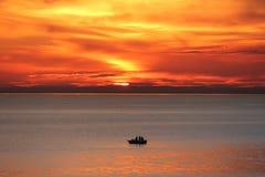 Black Rock Sunset. Three Fishemen watch deep multilayed orange sunset at end of working week in Winter at Black Rock in Melbourne, Australia Royalty Free Stock Photo