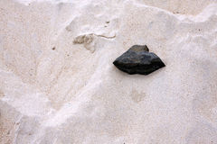 Black rock in white sand. Black stone in white sand on a beach in Brittany in France Stock Image