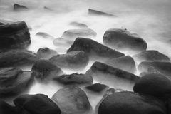 Black Rocks. Black and white abstract shot showing black rocks in a misty ocean Stock Images