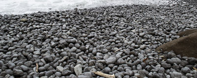 Black Rocks on a Beach Royalty Free Stock Photo