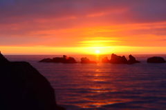 Black Rocks in Body of Water Under Orange Sunset Stock Photo