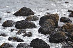 Black Rocks Dotting the Coastline. Coastline in Northern Ireland near Giant's Causeway Royalty Free Stock Image