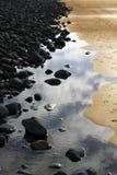 Black rocks gold sand. An irish beach at dawn stock photography