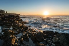 Black Rocks Beside Large Body of Water during Sunrise Royalty Free Stock Photography