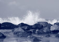Black rocks protecting coast against crashing white waves Stock Photos