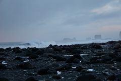 Black Rocks With Smashing Waves In The Background At Reynisfjara Beach In Iceland stock images