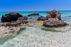 Black rocks and turquoise water, island of Crete Royalty Free Stock Image