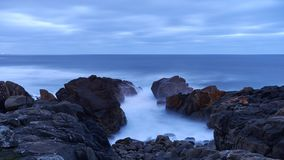 Black rocky cost at blue hour stock images