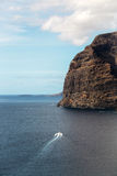 Black rocky island in blue sea Royalty Free Stock Images