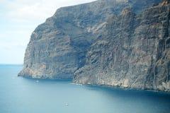 Black rocky island in blue sea Royalty Free Stock Photo