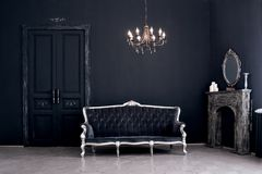 Black room in the castle. Black room in the castle with a vintage door, a chandelier, a sofa  and amirror and fireplace. Space where you can mount a person Stock Images