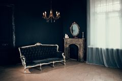 Black room in the castle with a window, a chandelier, a sofa and mirror and fireplace. Space where you can put a person Stock Photography