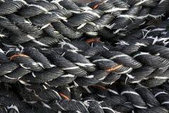 Black rope. Black beaten rope with white and orange fibers,cordage Stock Images