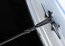 Black rope cleat. Mooring cleat with a black synthetic rope attached Royalty Free Stock Images