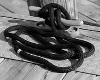Black Rope in Nautical Knot in Saugatuck. Pier on diamond plate and weathered wood with interesting shapes Royalty Free Stock Photography