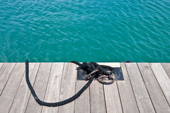 Black Rope Tied to Iron Rings on Edge of a Dock Royalty Free Stock Photography