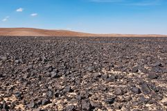 Black roscks in desert Stock Image