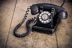 Black rotary phone. Old vintage rotary phone on a wood surface royalty free stock photography