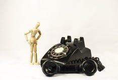 Black Rotary Telephone Beside Beige Manekin Stock Images