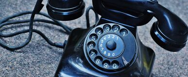 Black Rotary Telephone at Top of Gray Surface Royalty Free Stock Photography
