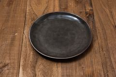 Black Plate on brown wooden background side view. Black Round Plate on brown wooden table background side view Stock Photo