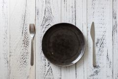 Black Plate on white wooden background with utensils Royalty Free Stock Photography