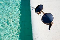 Black round sun glasses on pool board Royalty Free Stock Photo
