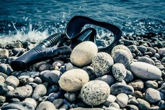 The black rubber driver`s mask and the snorkel lie on the seashore at the water`s edge Royalty Free Stock Photos