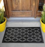 Black Rubber Ellipse Design Eyes Floor Door Mat outside home with yellow flowers and leaves. Black Rubber Ellipse Design Eyes Floor Door Mat outside home with royalty free stock photo