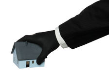 Black rubber glove taking a house Stock Image